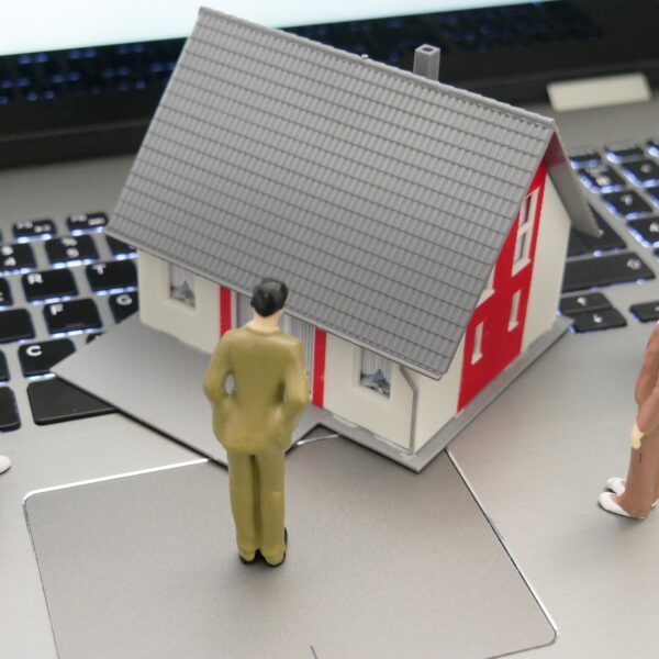 A model house and people figurines on top of a laptop keyboard