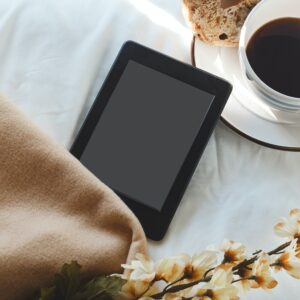 An eReader, next to a blanket, some flowers, and cup of tea and a muffin