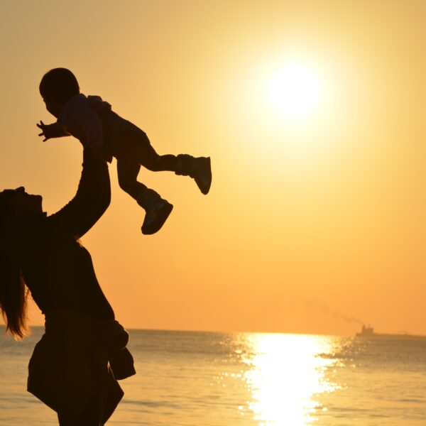 Woman carrying baby at the beach during sunset