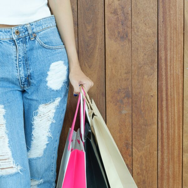A woman wearing a white shirt and ripped jeans carrying shopping bags