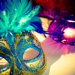 A venetian mask next to a candle
