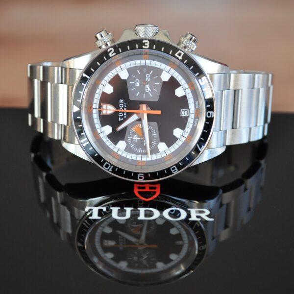 Tudor Geneve watch on a table with the Tudor logo on it