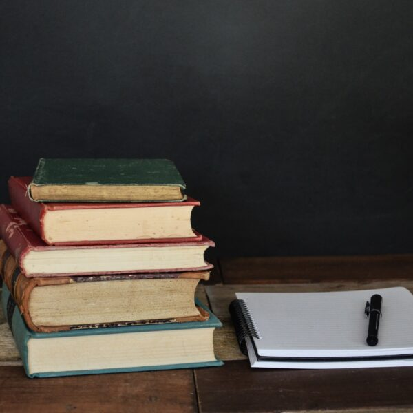 A stack of old books next to a notepad and pen