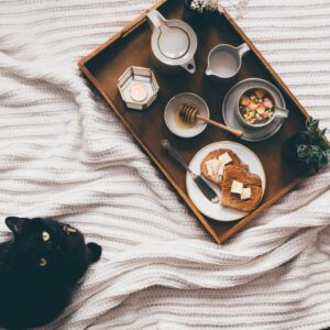 A cat and a breakfast tray on a bed with a tealight, tea, toast, honey and a plant next