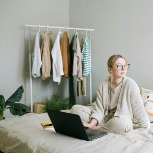 Woman in a sweater using a laptop on bed