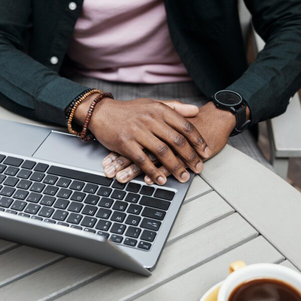 A man using a laptop with a cup of coffee next to him