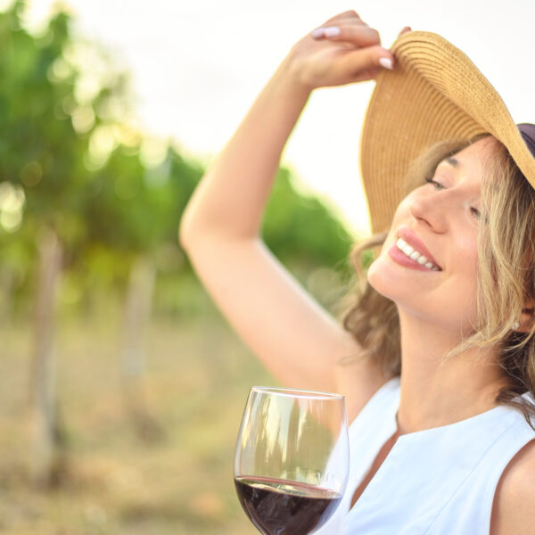 Woman wearing a sunhat whilst holding a glass of red wine