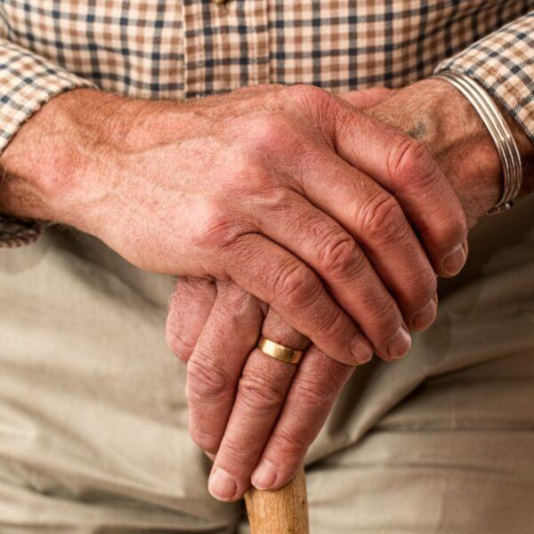 Elderly man leaning on a walking stick