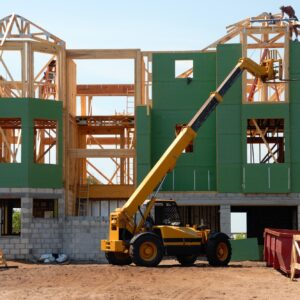 A man building a house with a cherry picker in the foreground