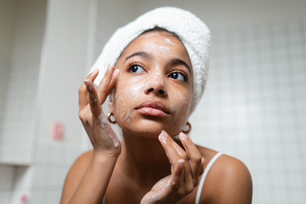 Woman with her hair wrapped in a towel washing her face
