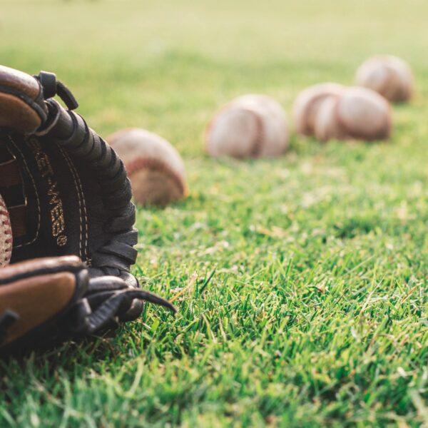 Baseball mitt and balls on a grass field