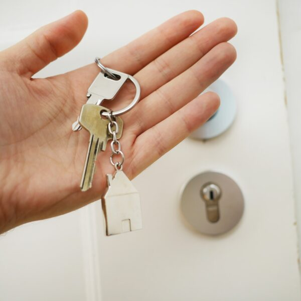 Hand in front of door holding keys with a house keychain on it