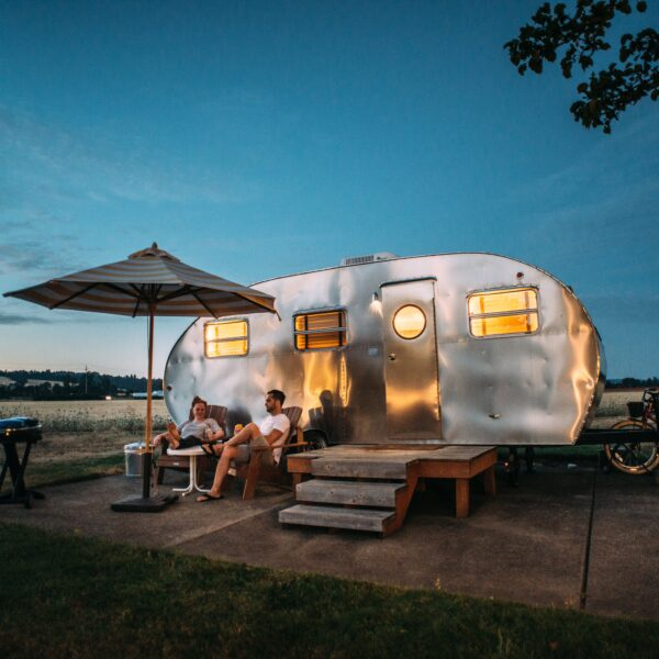 Man and woman sat in front of RV trailer