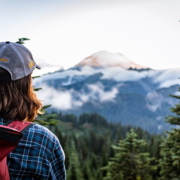 Young hiker overlooks the sunsetting on Mount Rainier wearing a Seattle to Portland biker's trucker-cap and hiking bag