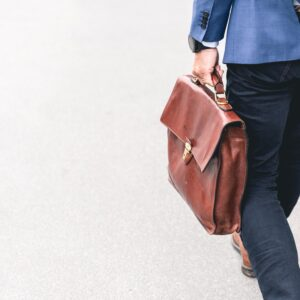 Person walking whilst holding a brown leather bag