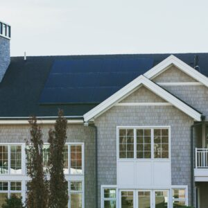 Solar Panels on a large seaside home with chimney and many windows