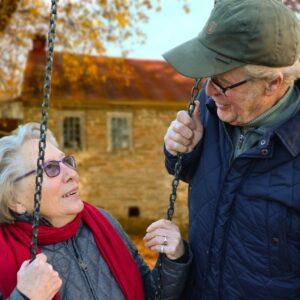 Elderly woman sitting on swing talking to an elderly man