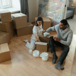 Happy couple unpacking their belongings surrounded by moving boxes