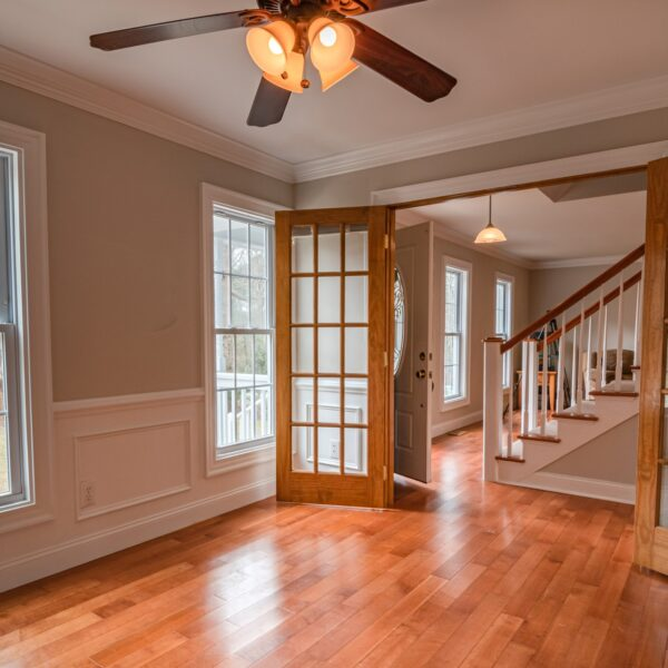 Photo of a living room with wooden flooring, with the open doorway showing the hallway, front door, and staircase