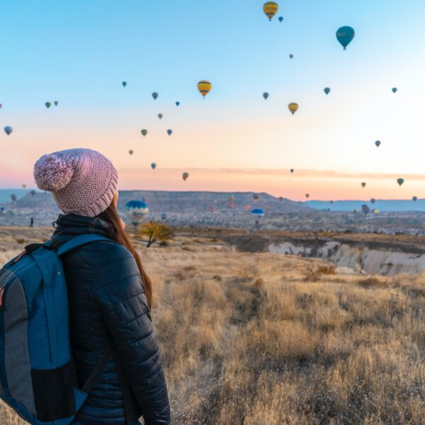 Woman watching hot air balloons rise into the air