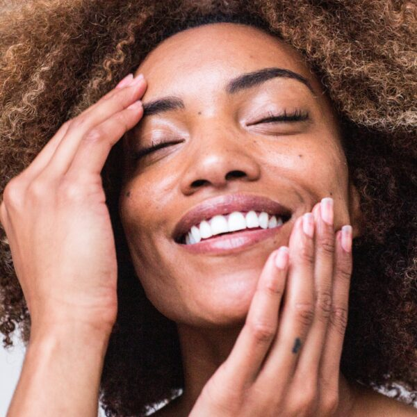 Woman smiling and touching her own face