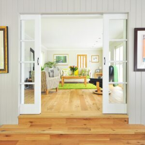 Photograph of an entryway with stairs looking into a living room with white, brown and green décor