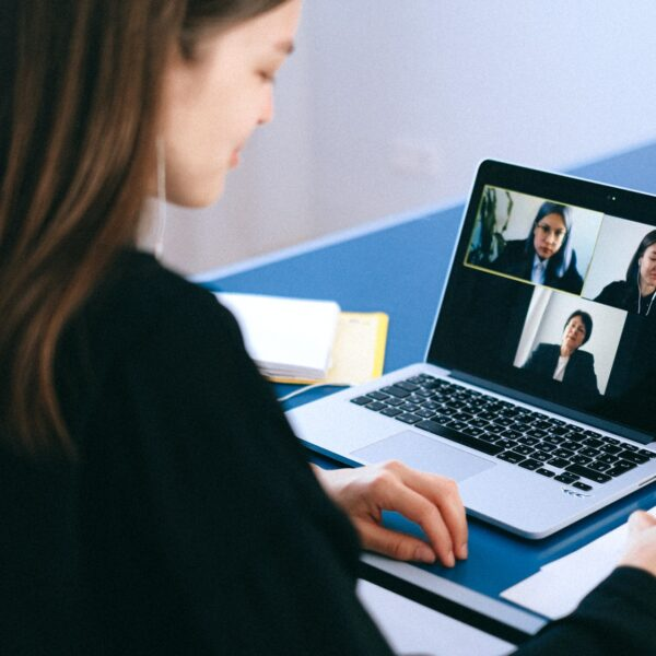 A woman on a video call with three other women