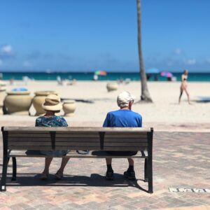 retired couple sitting on a bench looking at the beach