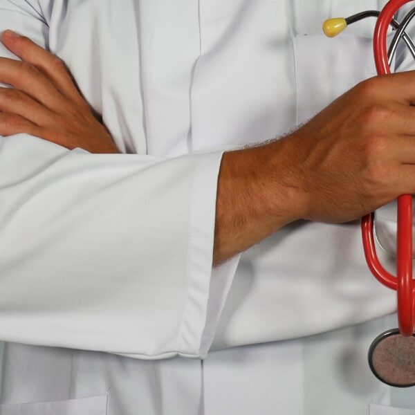 A doctor in a white coat holding a red stethoscope