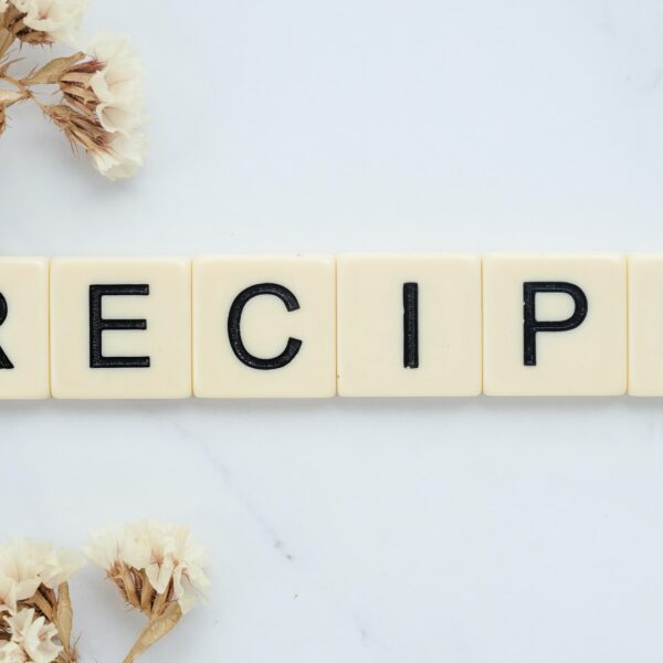 """Scrabble pieces spelling out """"recipe"""" with a marble background, surrounded by pale flowers"""