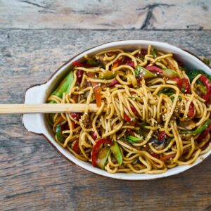 A bowl of stir fried noodles and vegetables with chopsticks on a wooden table